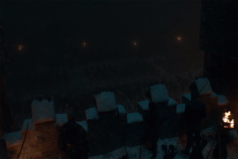 A still from Game of Thrones, showing a dimly-lit walkway over an extremely-dimly-lit battlefield.