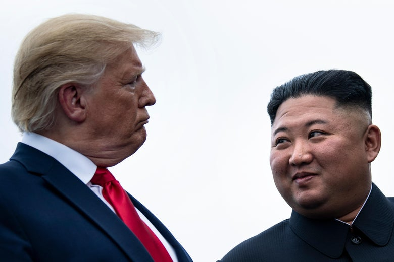 Trump and Kim looking at each other.
