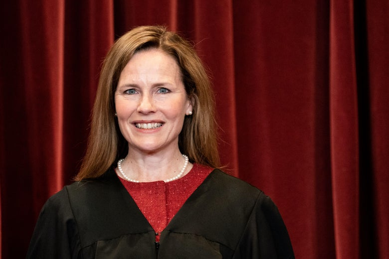 Justice Amy Coney Barrett wearing a robe during the group photo in front of a red velvet curtain.