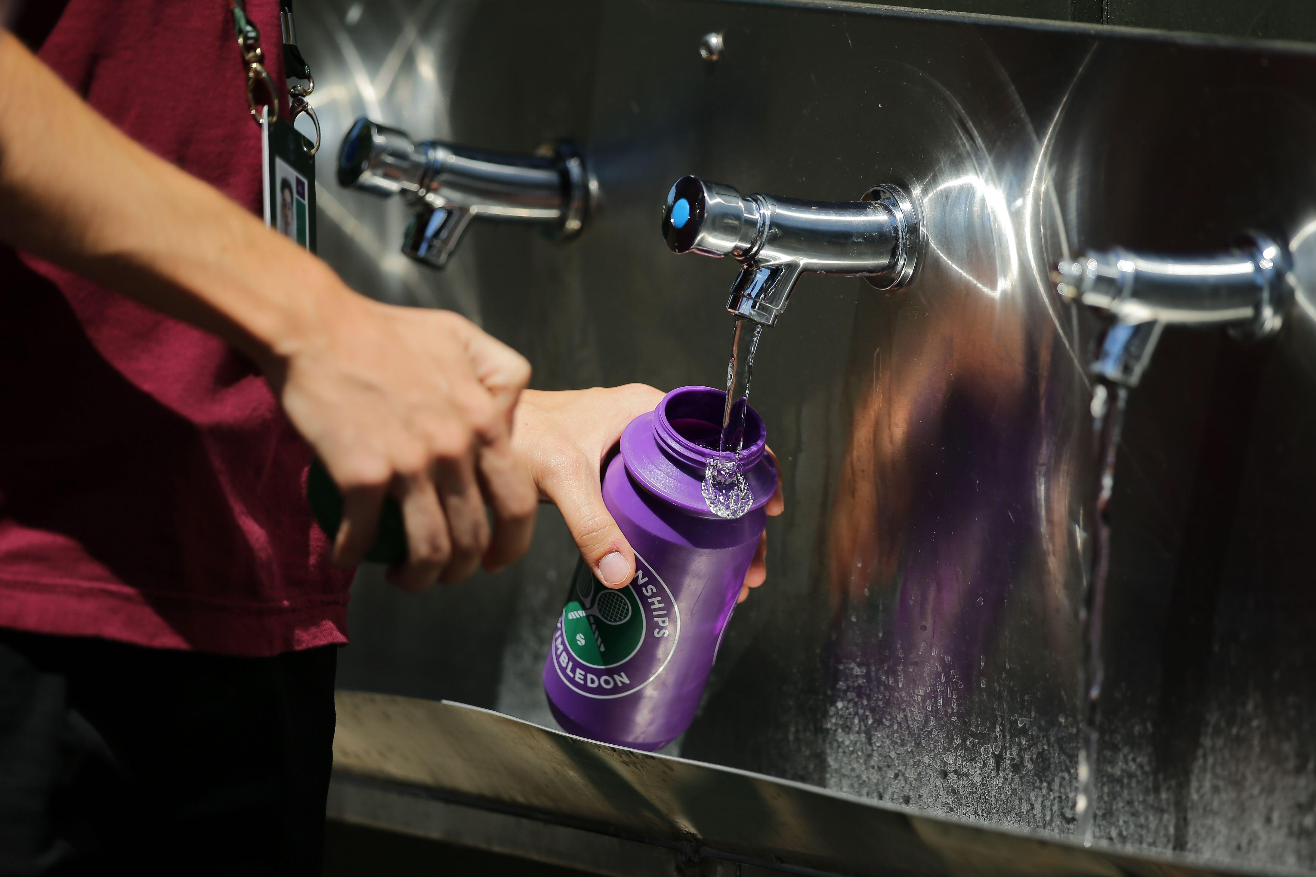 Person refilling a reusable water bottle with water.