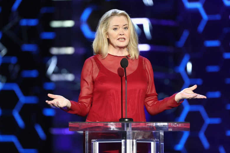 Cybill Shepherd stands at a podium, wearing a red dress.