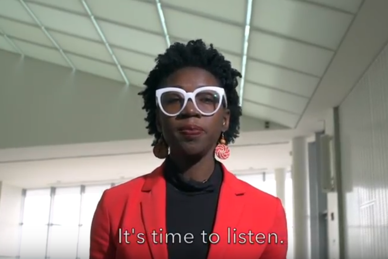 Joy Buolamwini wears white glasses, a black shirt, and a red jacket while standing in a hallway.