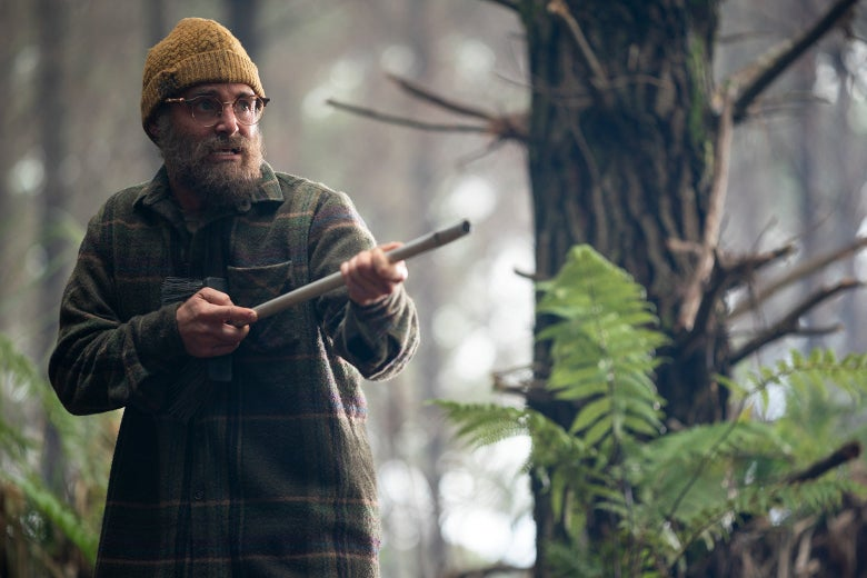Will Forte stands in the woods, brandishing a broom as if it were a gun, in a still from Sweet Tooth.