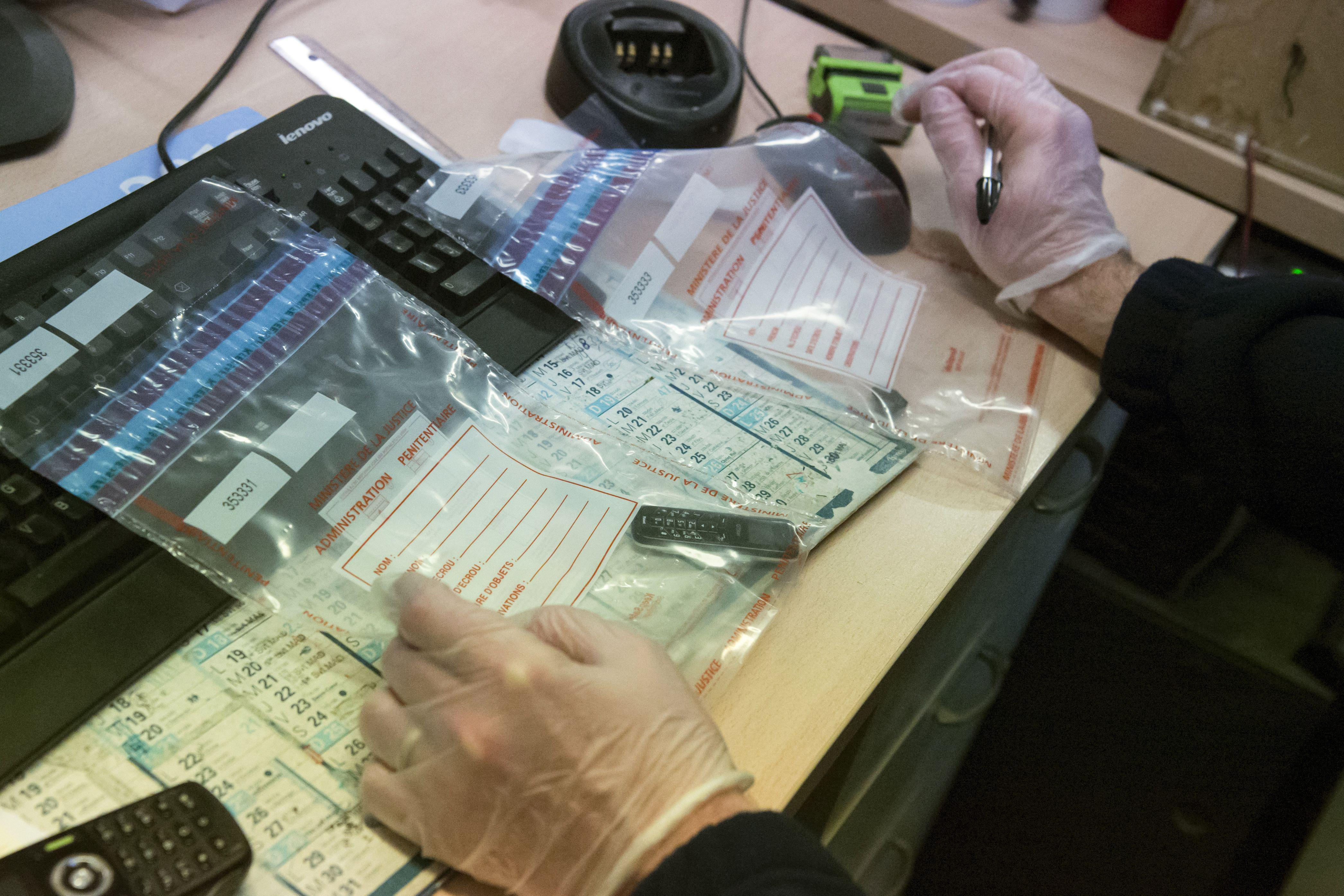 A prison supervisor registers a mobile phone found in a cell at the prison in Paris.