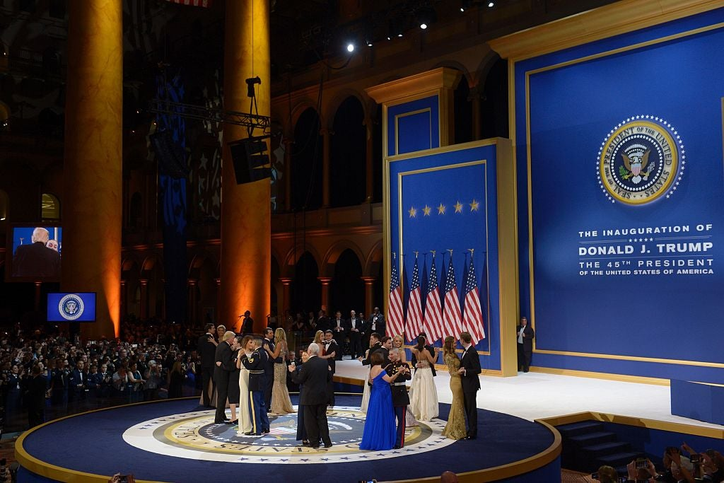 A wide shot of Donald and Melania Trump and several other couples dancing on a stage in a large hall with high ceilings.