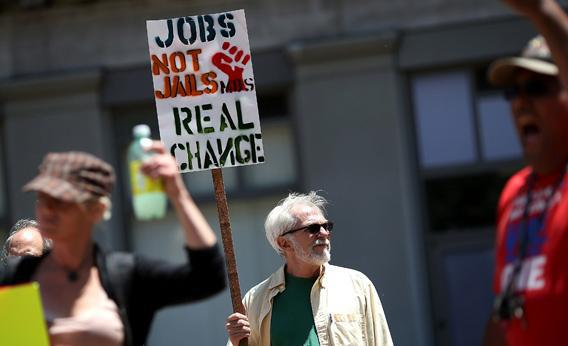 A protestor holds a sign during a demonstration against unemployment benefit cuts.