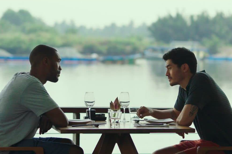 Parker Sawyers and Henry Golding sit across from each other at a set table. A lake recedes into the distance behind them.