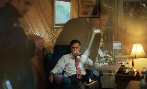 Staff members reflected off the window of the room where Republican presidential nominee Mitt Romney works before a campaign rally.