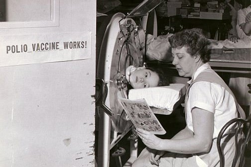 """A sign reads, """"Polio vaccine works,"""" beside a girl in an iron lung with a woman reading to her."""