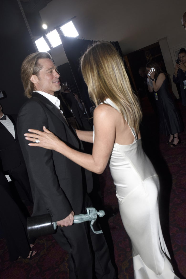 Brad Pitt and Jennifer Aniston smiling at each other.