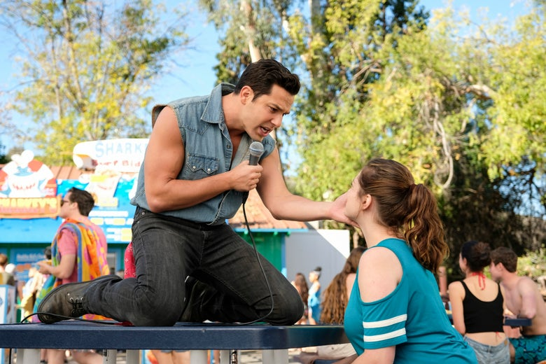 Greg, played by Skylar Astin, singing on top of a table to Rebecca, played by Rachel Bloom, in a scene from Crazy Ex-Girlfriend.