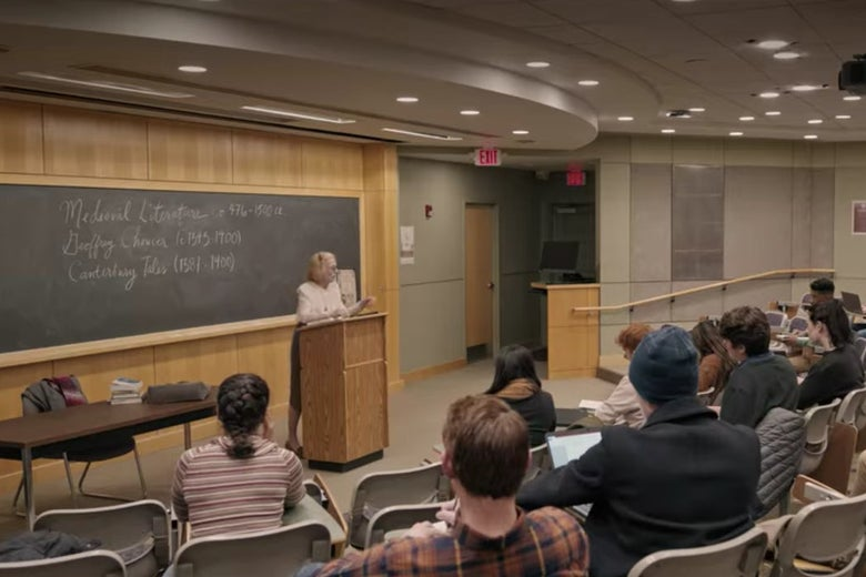 Joan teaching from a podium in a well-lit college classroom with rows of gray plastic chairs in it.