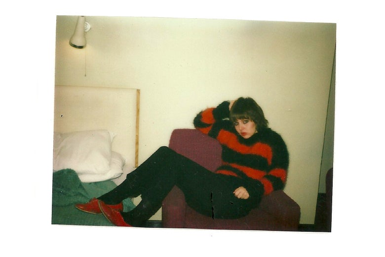 Amy Rigby lounging in a chair in her red-and-black striped sweater at the Strand Palace Hotel in 1978.