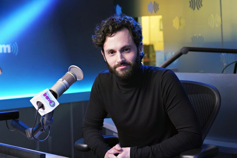 Penn Badgley sitting in front of a mic in a studio.