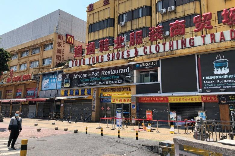 A person in a face mask walks near a shopping complex featuring an African Pot Restaurant.