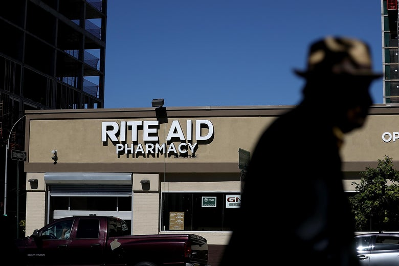 "A pedestrian, silhouetted, walks by a dark red pick up truck and a beige storefront with a white sign that reads, ""Rite Aid Pharmacy."""