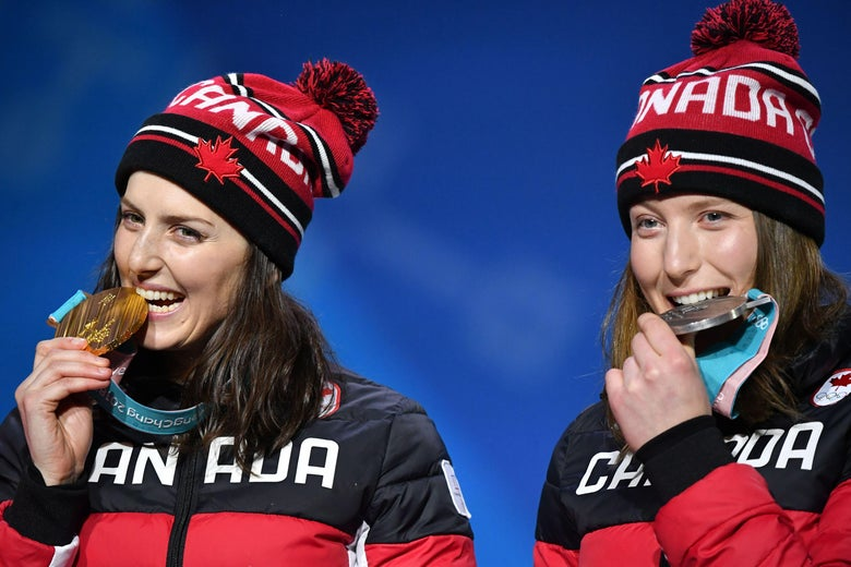 Canada's silver medallist Brittany Phelan and Canada's gold medallist Kelsey Serwa (L) bite their medals on the podium during the medal ceremony for the freestyle skiing Women's Ski Cross at the Pyeongchang Medals Plaza during the Pyeongchang 2018 Winter Olympic Games in Pyeongchang on February 23, 2018. / AFP PHOTO / Dimitar DILKOFF        (Photo credit should read DIMITAR DILKOFF/AFP/Getty Images)