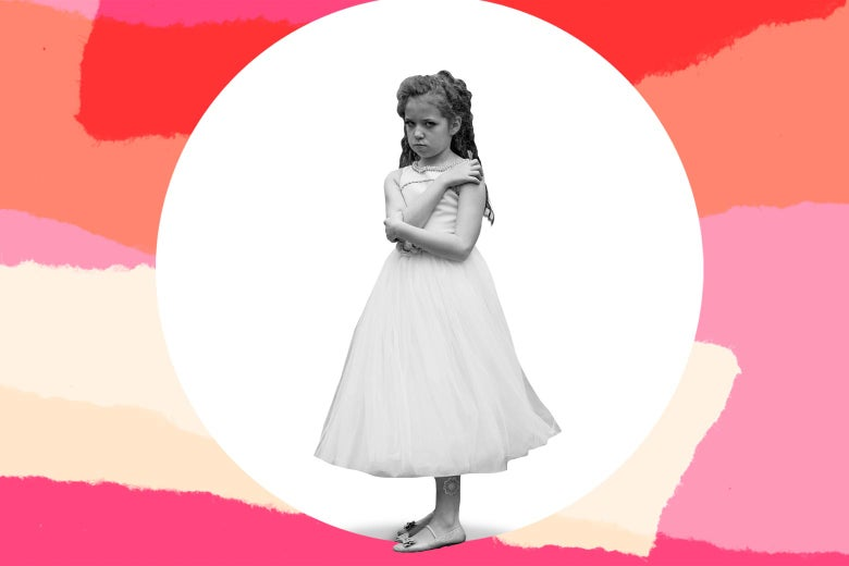 A young girl in a dress looking miserable