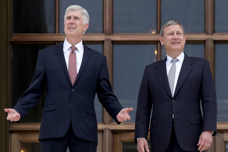 Neil Gorsuch and John Roberts stand and look out at the distance. Gorsuch is raising his hands.
