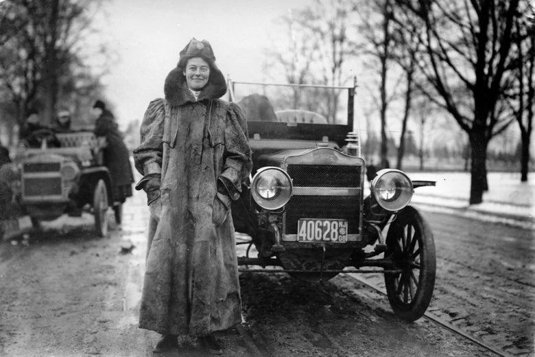 A woman in a full-length coat stands smiling in front of an old-timey car.