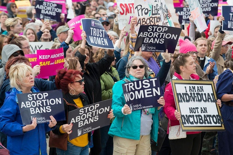 """Women holds signs promoting the right to abortion access, including """"trust women."""""""