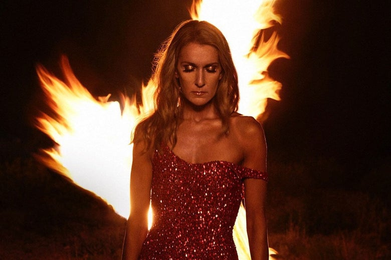 Celine Dion looks downward as a fire rages behind her.