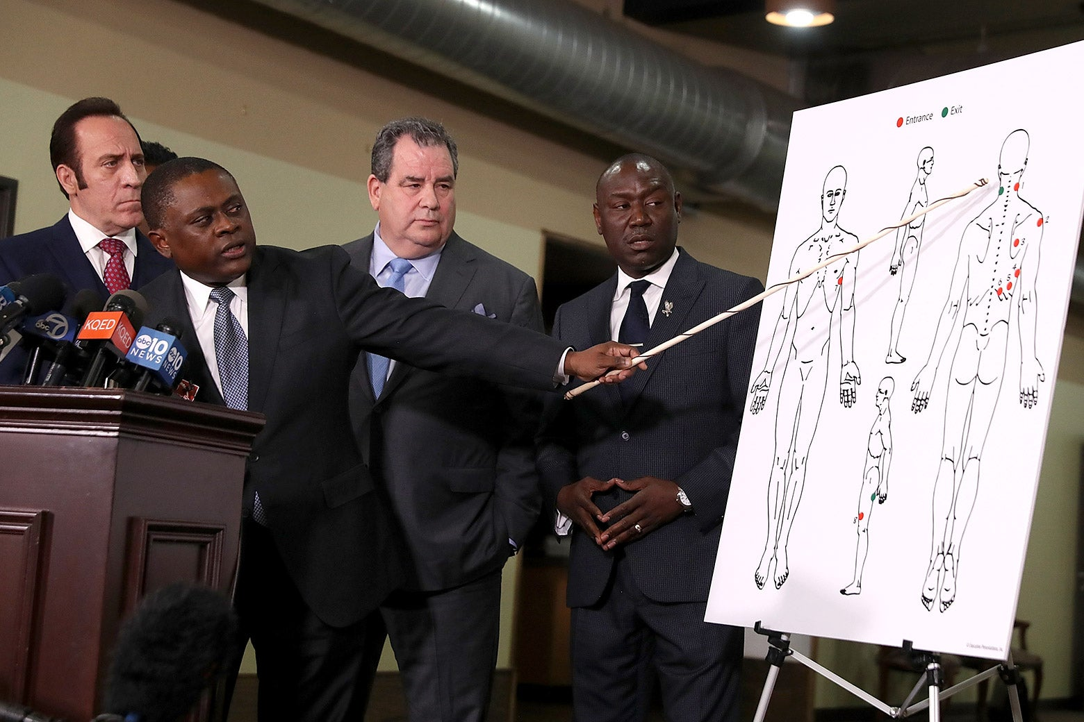 (L-R) Attorney Dale Galipo, Dr. Bennet Omalu, attorney Brian Panish and attorney Ben Crump examine a picture showing gunshot wounds to Stephon Clark during a news conference at the Southside Christian Center on March 30, 2018 in Sacramento, California.
