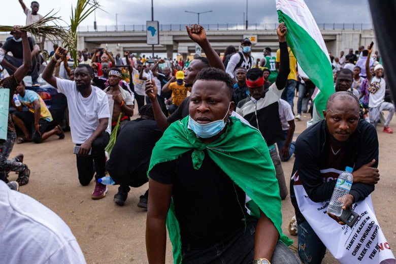 A man wearing a Nigerian flag and a face mask takes a knee while others raise their fists as a sign of protest.