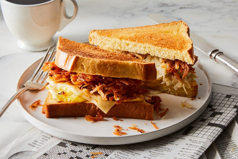 Latke, egg, and cheese sandwich sliced into triangles on a plate with a newspaper crossword folded under it and a coffee cup on the table beside it.