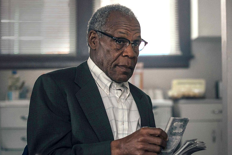 Danny Glover as Teddy Green, holding cash.
