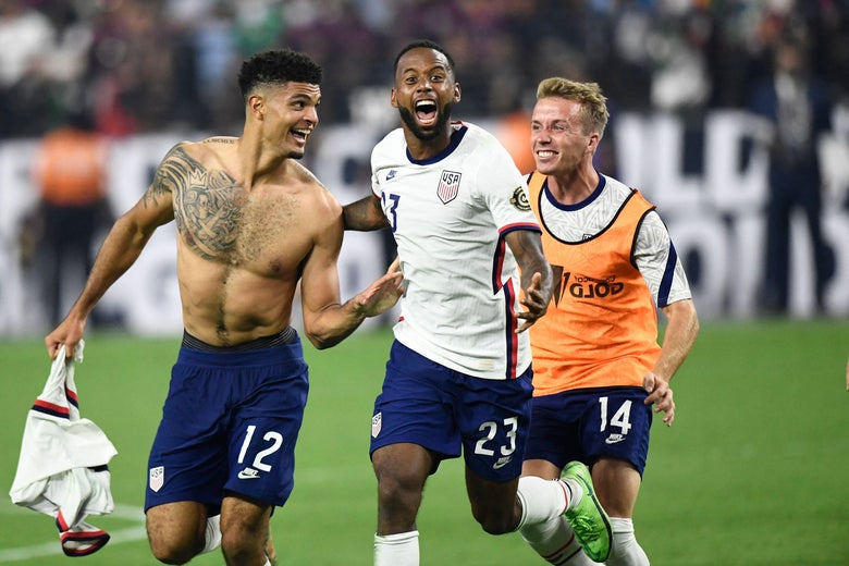 Shirtless and tattooed Miles Robinson, screaming Kellyn Acosta, and smiling Jackson Yueill run, embrace, and celebrate on the pitch.