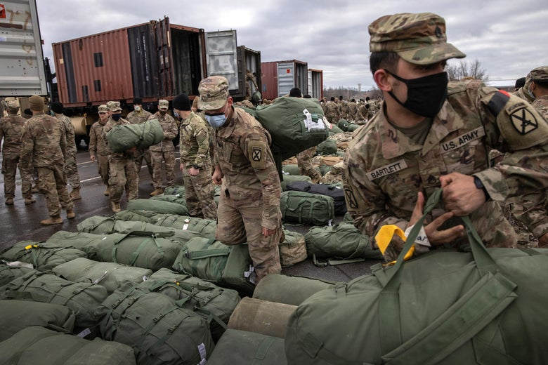 Soldiers in fatigues pick up their duffel bags, which are arranged in neat rows on the ground. There are shipping containers in the background.