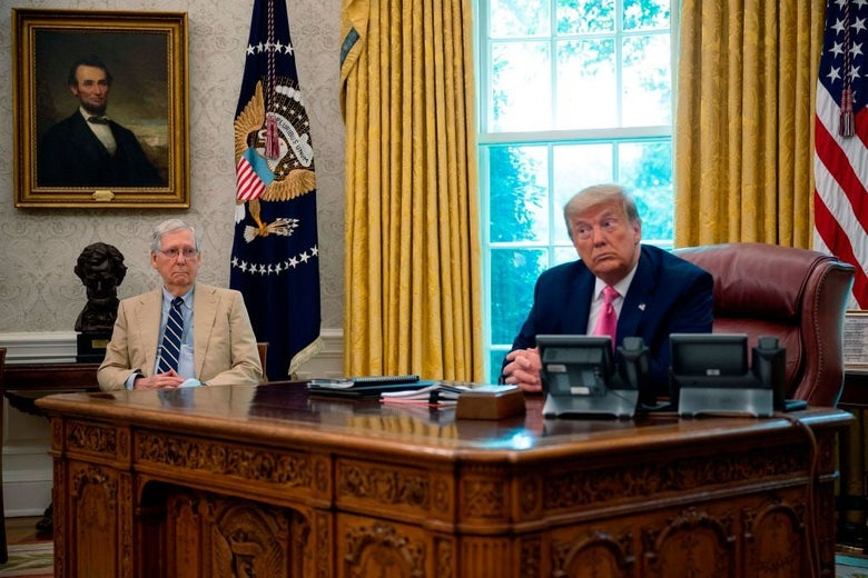 Trump, seated behind his desk, turns his head to listen to another speaker as McConnell looks on from a chair.