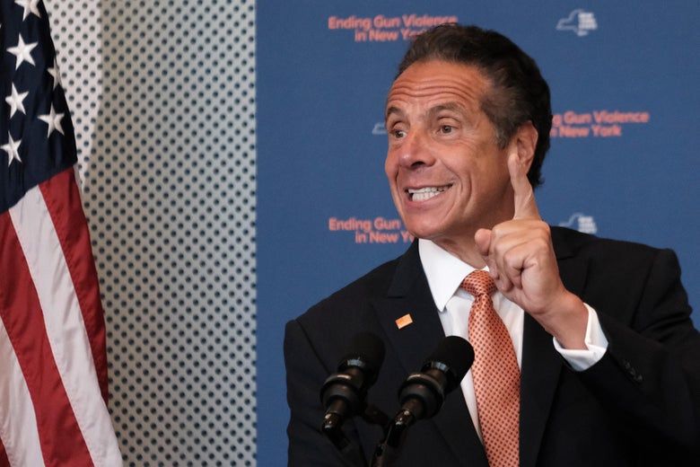 Cuomo speaks into microphones and points a finger upward.