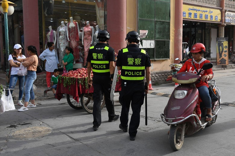 Police officers walk along a street near a fruit cart as a moped passes.