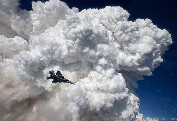 A towering pyrocumulus cloud provides a stunning backdrop for an Oregon Air National Guard F-15C fighter jet.