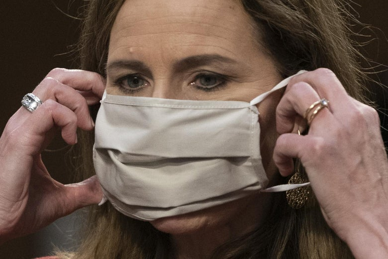 Barrett putting a beige cloth mask over her face.