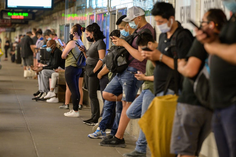 Commuters look at their mobile phones as they wait for a subway train in New York.