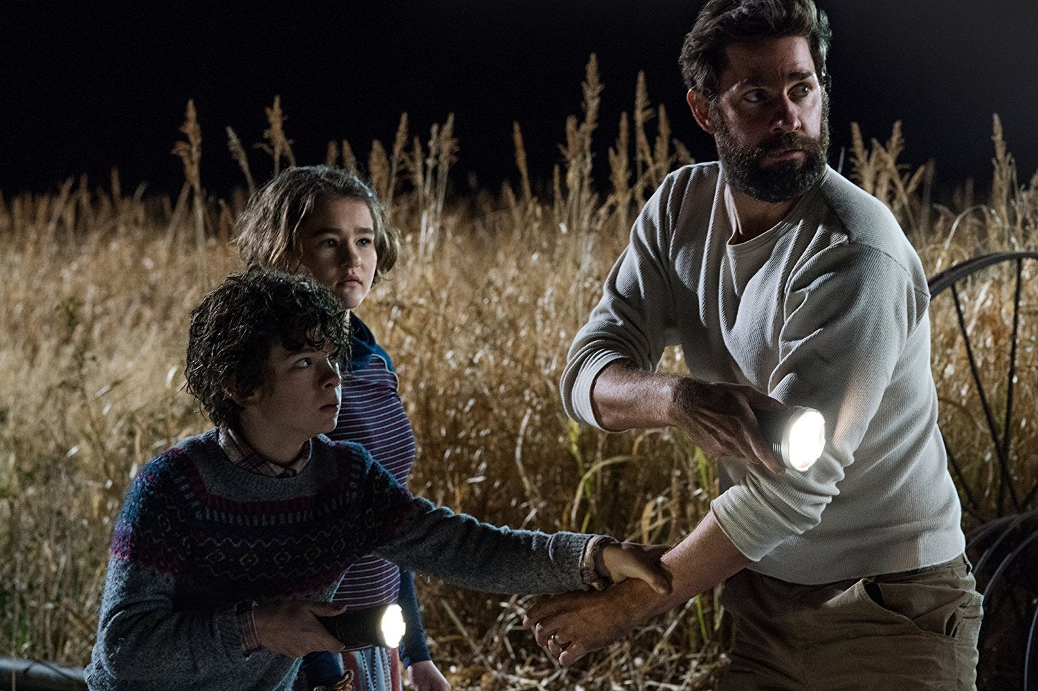 John Krasinski and the kids from A Quiet Place stand in a field of corn, looking terrified. John Krasinski and his son both brandish flashlights. They are looking off to the right. The son grip John Krasinski's arm.