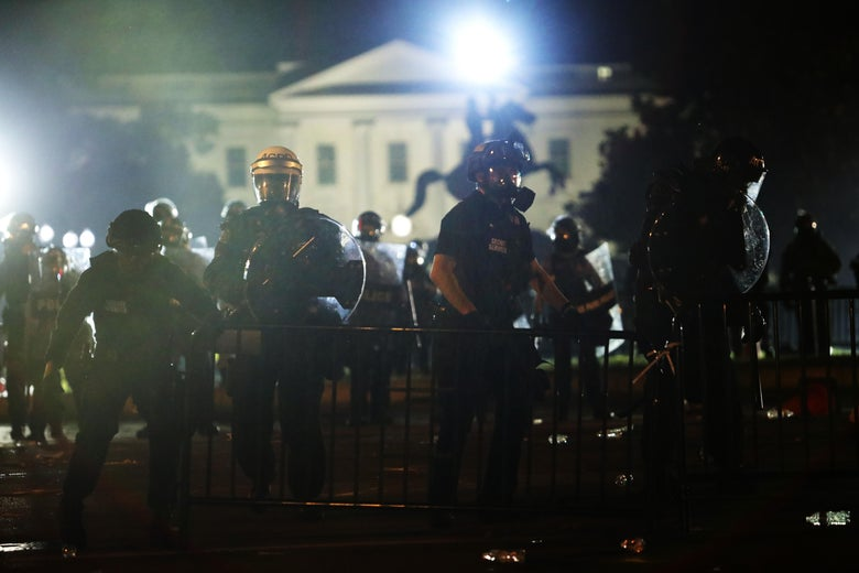 A number of police officers in riot gear stand in front of the White House.