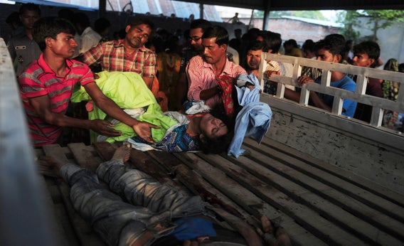 Bangladeshi volunteers and workers load dead bodies onto a truck at the site of a building collapse in Savar, on the outskirts of Dhaka, on April 24, 2013.