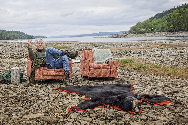 Anthony Bourdain sits in an upholstered chair on a rocky beach next to a bear rug.