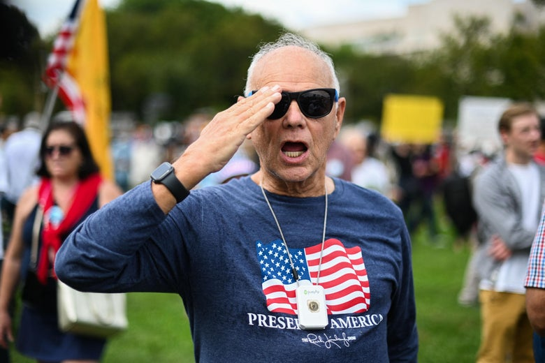 A man in a shirt with an American flag on it salutes as he stands in a small crowd of people.