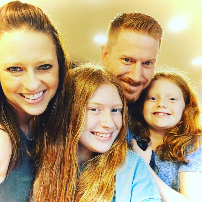 A family selfie with a woman, a man, and two girls.