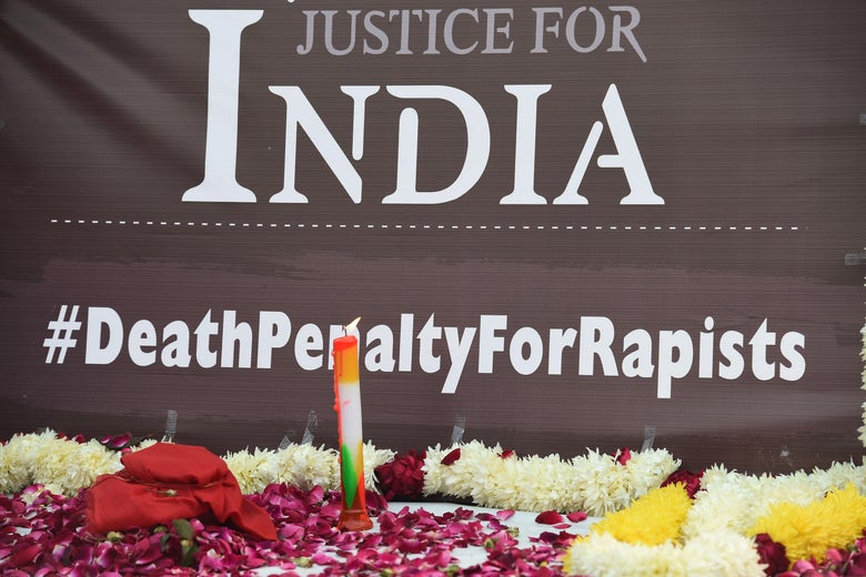 """A candle lit by demonstrators is seen in front of a banner reading """"Justice for India"""" and """"#DeathPenaltyForRapists."""""""