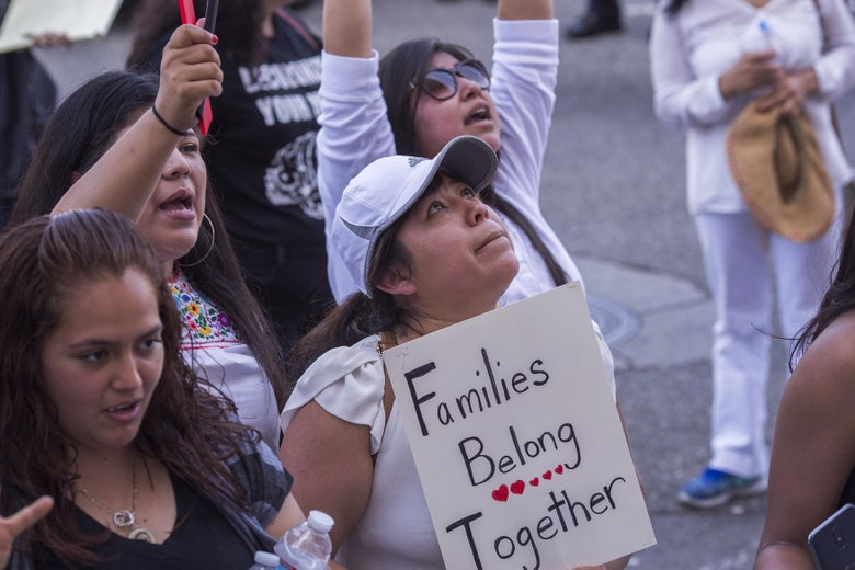 "A protester's eyes well up as she holds a ""Families belong together"" sign."