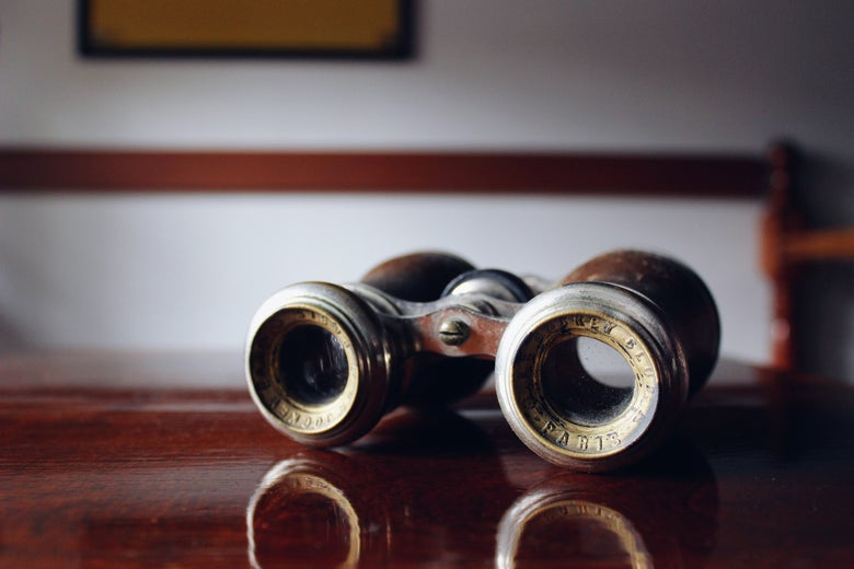 Old-fashioned binoculars sit on a wooden surface.