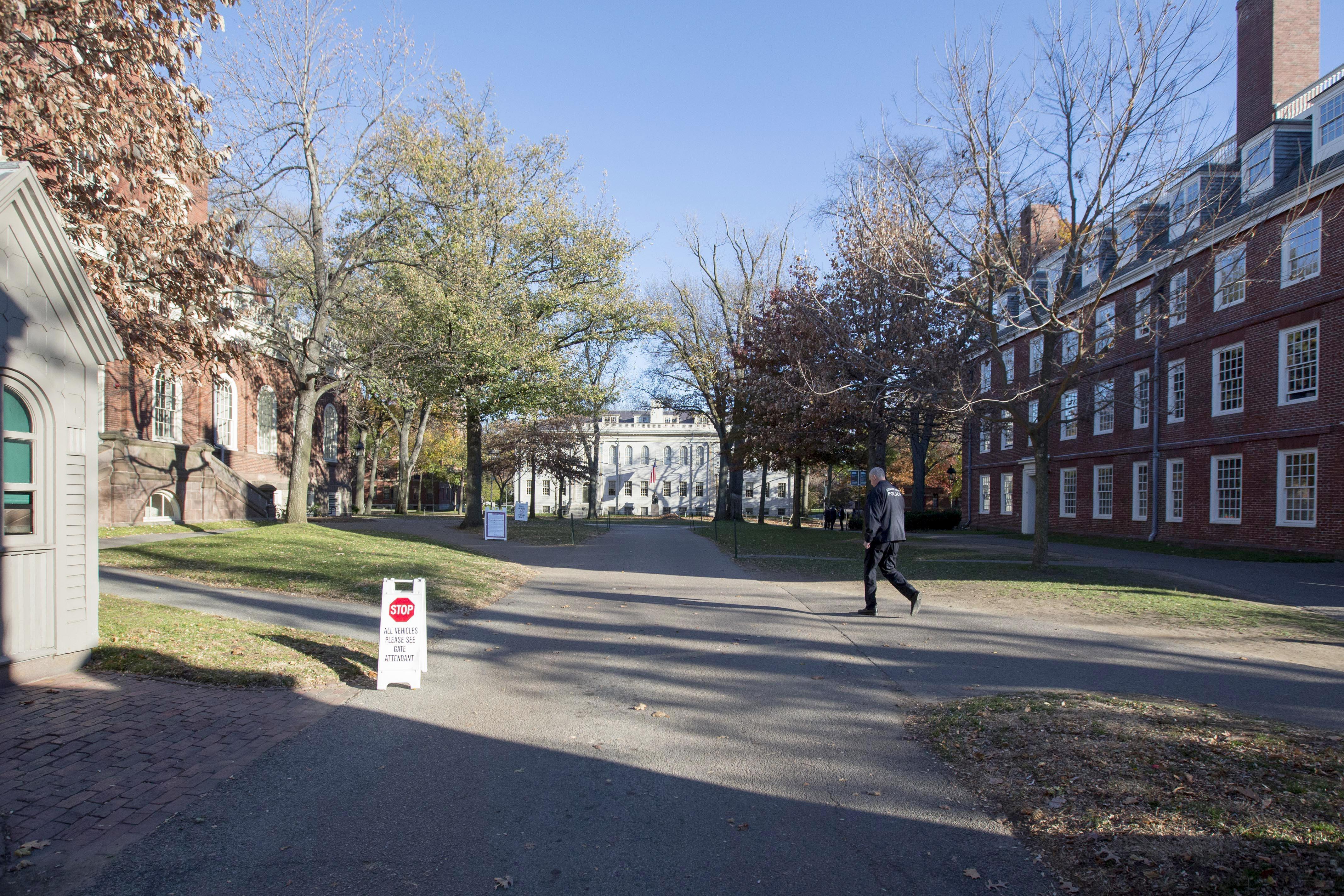 A Harvard University police officer walks through Harvard Yard.