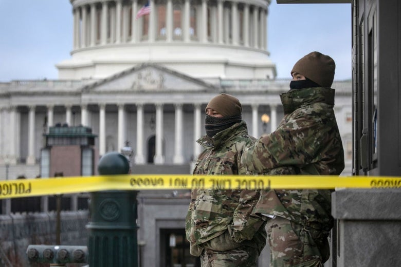 Two men in camouflage coats stand behind yellow police tape against the backdrop of the Capitol dome.