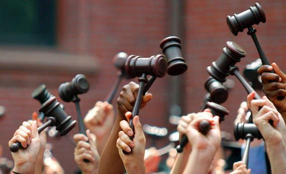Graduates from the law school hold up gavels in celebration during their commencement at Harvard University in Cambridge, Mass., May 27, 2010.
